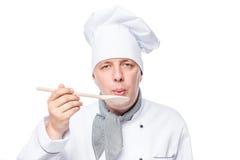 Szef kuchni je naczynie na drewnianej łyżce na bielu obraz royalty free