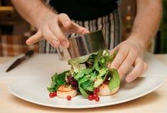 Szef kuchni jest kulinarnym zakąską z przegrzebkami fotografia stock