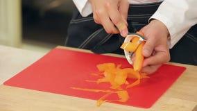 Szef kuchni jest strugający marchewka i pokrajać zdjęcie wideo