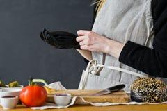Szef kuchni jest ubranym r?kawiczki wi?nia Poj?cie gotowa? czarnego hamburger Kuchnia, boczny widok, przestrze? dla teksta obraz royalty free
