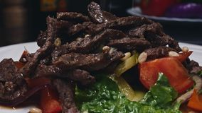 Szef kuchni jest wykończeniowego posiłku wołowiny teasty stkiem z sałatką dla gościa restauracja Definitywny dotyk w 4k zbiory