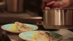 Szef kuchni kończy jej talerza i prawie przygotowywający słuzyć przy stołem Tylko ręki W końcu naczynie opatrunek: stku mięso z zbiory