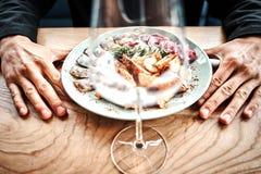 Szef kuchni kończy jej talerza i prawie przygotowywający słuzyć przy stołem Tylko ręki W końcu naczynie opatrunek: stku mięso, ry fotografia royalty free