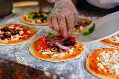 Szef kuchni który stawia polewy na pizzy, Zdjęcie Royalty Free