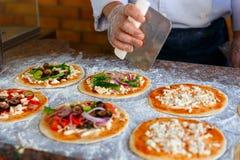 Szef kuchni który stawia polewy na pizzy, Obrazy Royalty Free