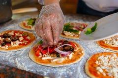 Szef kuchni który stawia polewy na pizzy, Fotografia Royalty Free