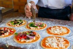 Szef kuchni który stawia polewy na pizzy, Zdjęcia Stock