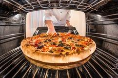 Szef kuchni kulinarna pizza w piekarniku Zdjęcia Stock