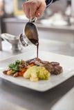 Szef kuchni matrycuje w górę jedzenia w restauraci Zdjęcia Stock