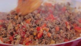 Szef kuchni miesza smażący zmielonego mięso z pokrojonymi cebulami i pomidorami zbiory