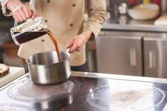 Szef kuchni nalewa brown ciecz w rondlu Zdjęcia Stock