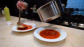 Szef kuchni nalewa czerwoną polewkę zbiory