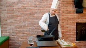 Szef kuchni nalewa jarzynowego olej niecka, opowiada kamera Obrazy Stock