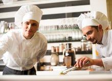 Szef kuchni ogląda jego pomocniczego ułożenia naczynie Fotografia Royalty Free