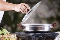 Szef kuchni otwiera dekiel garnek przed kulinarnym kluski zdjęcie stock