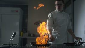 Szef kuchni podpala w górę flambe na gorącej niecce przy kuchnią w zwolnionym tempie, dużym otwiera ogień w kuchni, niecka  zbiory