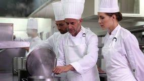 Szef kuchni pokazuje kolega zawartość garnek i ono uśmiecha się przy kamerą zdjęcie wideo