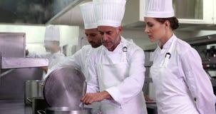 Szef kuchni pokazuje kolega zawartość garnek i ono uśmiecha się przy kamerą zbiory