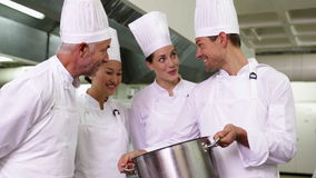 Szef kuchni pokazuje kolegom zawartość wielki garnek zbiory