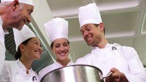 Szef kuchni pokazuje kolegom zawartość wielki garnka niskiego kąta widok zdjęcie wideo