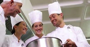 Szef kuchni pokazuje kolegom zawartość wielki garnka niskiego kąta widok zbiory wideo