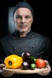 Szef kuchni pokazuje warzywa na tnącej desce Fotografia Stock