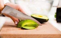 Szef kuchni pokrajać avocado zakończenie Obrazy Royalty Free