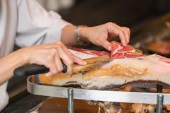 Szef kuchni pokrajać serrano baleron nad hiszpańskim serrano biel odosobniony baleronu jamon Typowy Hiszpański delikatny Obrazy Stock