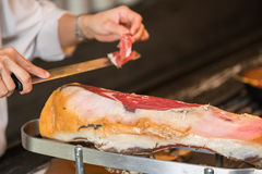 Szef kuchni pokrajać serrano baleron nad hiszpańskim serrano biel odosobniony baleronu jamon Typowy Hiszpański delikatny Fotografia Royalty Free