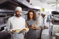 Szef kuchni przedstawia jego jedzenie talerze Zdjęcia Stock