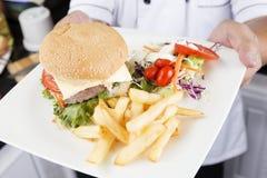 Szef kuchni przedstawiający talerz hamburger zdjęcia stock