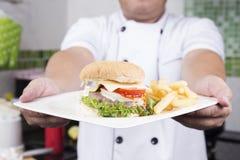 Szef kuchni przedstawiający talerz hamburger fotografia stock