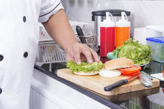 Szef kuchni przygotowywał plasterek sałata na hamburger babeczce zdjęcia stock