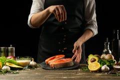 Szef kuchni przygotowywa świeżej łosoś ryby, smorgu pstrąg, kropi czarnego pieprzu z składnikami Mróz w powietrzu ryby gotowania zdjęcie stock