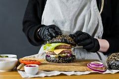 Szef kuchni przygotowywa ogromnego hamburger Pojęcie gotować czarnego cheeseburger Domowej roboty hamburgeru przepis obrazy stock