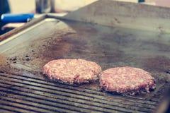 Szef kuchni przygotowywa smakowitych hamburgery przy plenerowym stojakiem Obrazy Stock