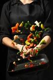 Szef kuchni przygotowywa warzywa na niecce Czarny tło dla kopiowego teksta Restauracyjny biznes i reklama fotografia stock