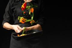 Szef kuchni przygotowywa warzywa na niecce Czarny tło dla kopiowego teksta Restauracyjny biznes i reklama obraz royalty free