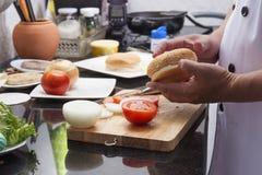 Szef kuchni przygotowywający hamburger przed kulinarnym hamburgerem Zdjęcia Royalty Free