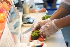 Szef kuchni ręka w rękawiczkowej kulinarnej gałęzatki mak rolce Zdjęcia Royalty Free