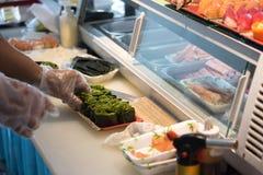 Szef kuchni ręka w rękawiczkowej kulinarnej gałęzatki mak rolce Zdjęcie Royalty Free