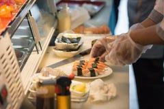 Szef kuchni ręka w rękawiczkowym kulinarnym gałęzatka suszi Obrazy Royalty Free