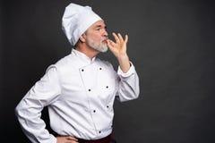 Szef kuchni robi smakowitemu wyśmienicie gestowi dotyka całować Ufny brodaty m?ski szef kuchni w bielu mundurze z doskonali? znak zdjęcia stock