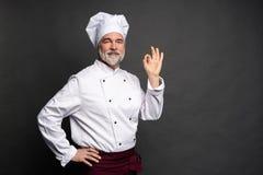 Szef kuchni robi smakowitemu wy?mienicie gestowi dotyka ca?owa? Ufny brodaty m?ski szef kuchni w bielu mundurze z doskonali? znak zdjęcia stock