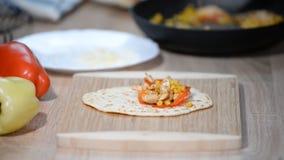 Szef kuchni robi tortilla z kurczakiem, kukurudzą i dzwonkowymi pieprzami, zbiory