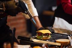 Szef kuchni robi wołowina hamburgerom przy hamburgeru pubem obrazy stock