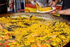 Szef kuchni stawia paella z owoce morza na talerzu przy ulicznym karmowym festiwalem obraz royalty free
