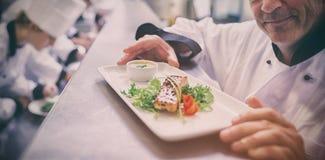 Szef kuchni szczęśliwy z skończonym naczyniem z praktykantami pracuje w kuchni Obraz Stock