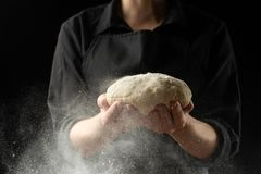 Szef kuchni trzyma ciasto dla chleba, pizza, cukierki Na czarnym tle W górę, Karmowy pojęcie fotografia royalty free