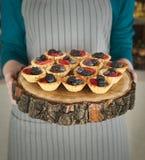 Szef kuchni trzyma drewnianą tacę z jagodowymi tartlets obrazy royalty free